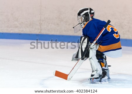 Youth ice hockey goaltender stands ready for the puck during a game