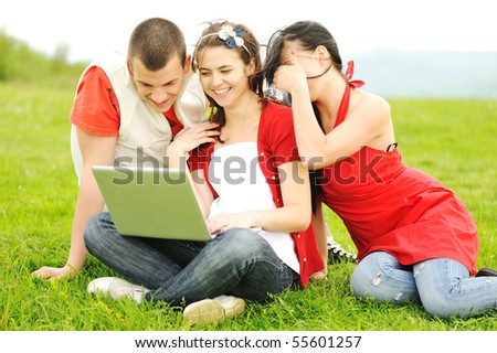 Youth on laptop together in nature - stock photo