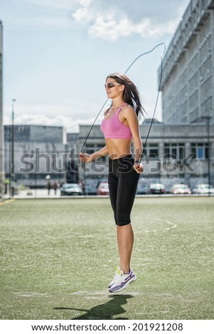 Youth on the move and jump. Young and charming woman in sunglasses and sportswear standing on the football field and jumps on the rope side view - stock photo
