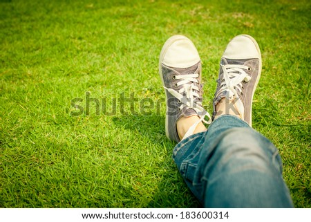 youth sneakers on girl legs on grass during sunny serene summer day. - stock photo
