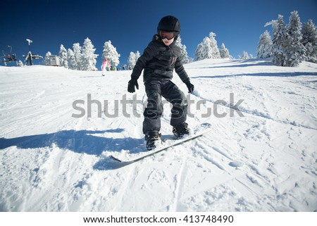 Youth snowboarder hitting the slopes - stock photo