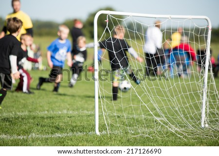 Youth Soccer - This is a shot of a youth soccer team and their coaches playing a game. Shot with a shallow depth of field with the focus set on the goal. - stock photo