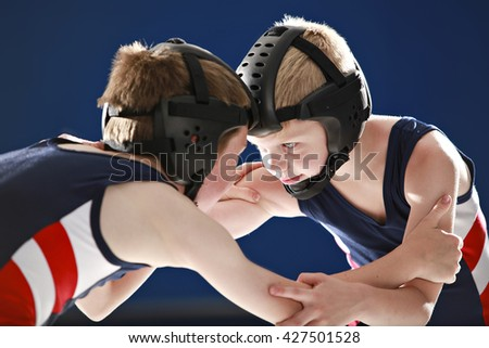 Youth wrestlers hand fighting on their feet - stock photo