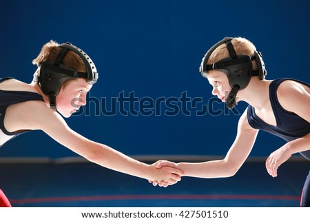 Youth wrestling partners shaking hands - stock photo
