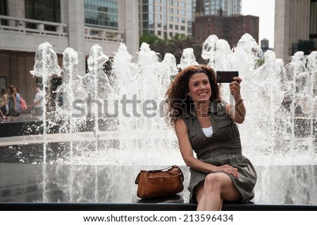 Youthful brunette taking selfie by the fountain - stock photo