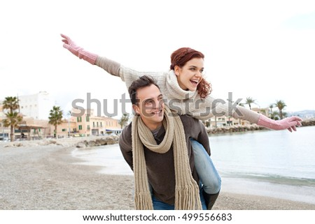 Youthful happy tourist couple playful carrying piggy back on beach, autumn winter holiday, wearing jumpers laughing together, outdoors. Fun active recreation travel lifestyle, romantic relationship.