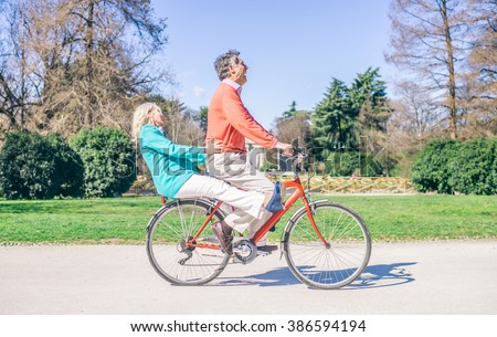 Youthful senior couple riding on a bicycle in a park - Two pensioners having fun and acting like young people  - stock photo