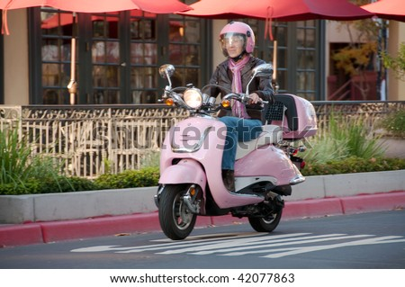 youthful sixty year old biker riding on a city street - stock photo