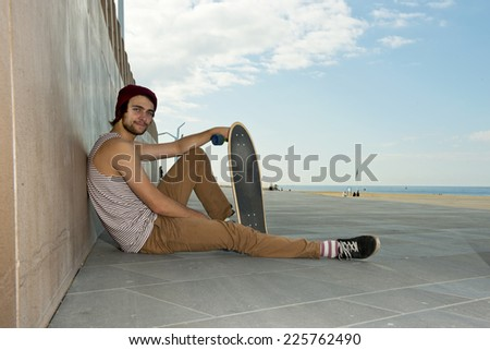 youthful skateboarder, relaxing carefree against a granite wall, with a magnificent view of the coastal line and sea.