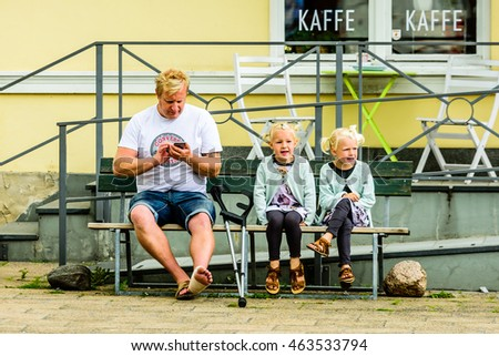 Ystad, Sweden - August 1, 2016: Real people in everyday life. Adult man with crutches and a hurt foot sit beside two lovely girls dressed to match on a public bench outside a coffee shop.