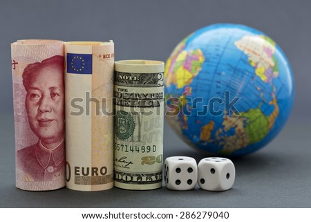 Yuan, euro, and collar next to black and white dice with globe in background.  When risks are worldwide, business and investment decision makers take into account larger, international strategies.  - stock photo