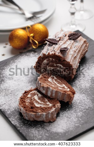 Yule log cake decorated with chocolate leaves on a Christmas table