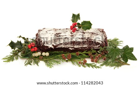 Yule log chocolate christmas cake with flora decoration of holly, ivy, mistletoe and cedar cypress leaf sprigs with pine cones over white background.