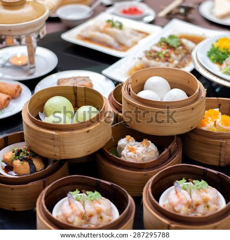 yumcha,The arrangement of various dim sum in bamboo steamer with chinese bun , pao , bao zi , steamed dumpling , shumai on table in chinese restaurant - stock photo