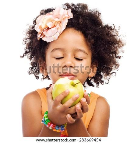 Yummy. Beautiful little girl eating green apple - stock photo
