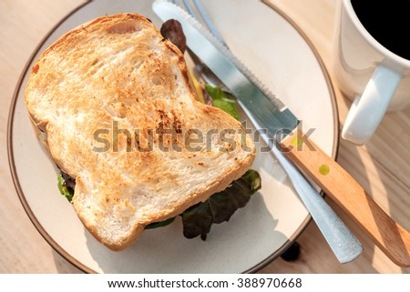 Yummy Beef and cheese Grilled Sandwich on round cream color plate with fork and knife place beside a cup of coffee on wooden table
