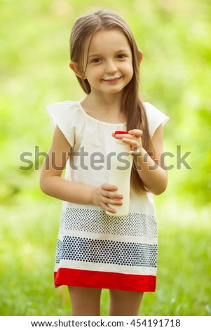 Yummy childhood concept. Smiling baby girl with long brown hair in white vintage summer dress drinking yogurt in the park, holding white plastic bottle. Outdoor shot