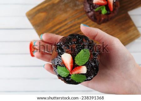 Yummy chocolate cupcake in hand, close-up - stock photo