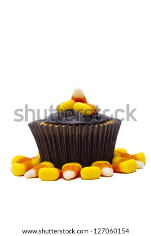 Yummy cupcake garnished with candy corn and chocolate cream displayed on white background. - stock photo