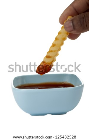 Yummy french fry dipped in a bowl of ketchup - stock photo