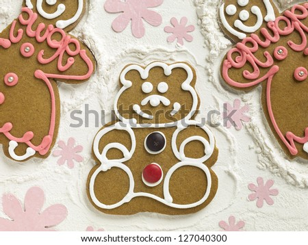 Yummy gingerbread cookies lying on flour decorated with flowers - stock photo