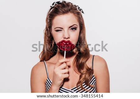 Yummy kiss. Beautiful young woman holding a lollipop in front of her mouth and winking while standing against white background - stock photo