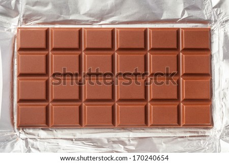 Yummy milk chocolate bar in open foil wrapping ready for eating. The foil is filled the frame of the image. - stock photo