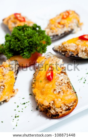 Yummy mussels under cheese  on white plate . - stock photo