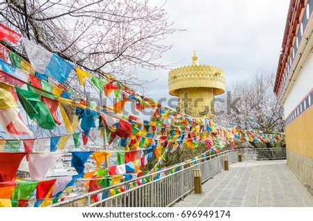 Yunnan,China - April 16,2017 : Biggest Tibetan prayer wheel with tibetan prayer flags at Dukezong Temple which is located at Shangri La, Yunnan China