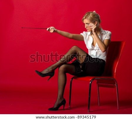 yuong woman teacher posing in studio on red background - stock photo