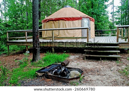 Yurt Camp Site built on a deck with in-ground fire ring in foreground.  DeGray Lake Resort State Park, Arkansas.  Taken shortly after rain shower. - stock photo