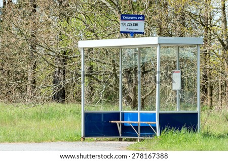 YXNARUM, SWEDEN - MAY 11, 2015: Empty bus stop shelter with small bench. Forest in background and high grass at sides. Sign on top of shelter with bus numbers and place name. - stock photo