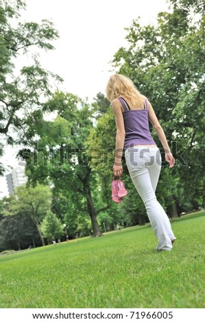 Yyoung woman holding her shoes and walking barefoot on grass in park - rear view