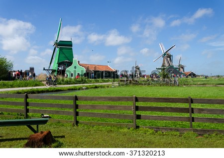 Zaanse Schans, Netherlands - May 5, 2015: Tourists visit Windmills and rural houses in Zaanse Schans, Netherlands. This village is a popular touristic destination in Netherlands