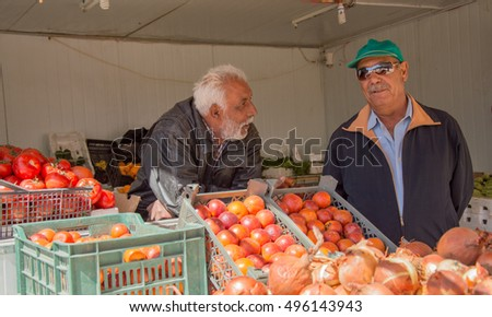 Zaatari Refugee Camp, Jordan - March 14, 2015: two unidentified refugee shop sellers talk each other near a vegetable stall set up in the main street of the Syrian refugee camp of Zaatari, Jordan.