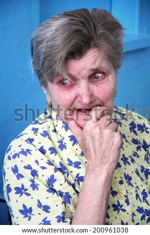 ZABOLOTTIA, UKRAINE - JUNE 11 - A sad old lady crying at shelter for single disabled people in Zabolottia on Julne 11, 2014.  - stock photo