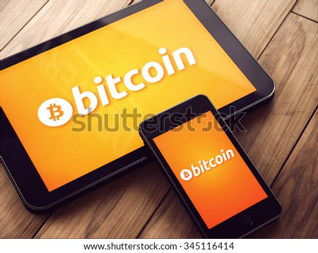 Zagreb, Croatia - CIRCA October , 2015: Close up shot of tablet and smartphone showing Bitcoin logo, on wooden table. Bitcoin crypto currency is peer to peer payment network.