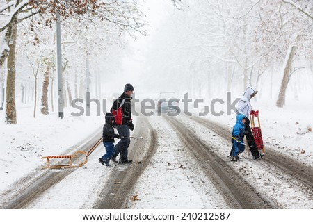 ZAGREB, CROATIA - DECEMBER 28, 2014: Family of four carefully crossing the street covered with snow and mud, during heavy snowstorm, heading for the park to enjoy and play with the kid.