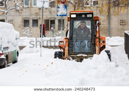 ZAGREB, CROATIA - DECEMBER 28, 2014: Snow plough cleaning pavements and streets of Zagreb which are covered in snow and mud during heavy snowfall, first snowstorm of 2014.