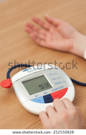 Zagreb, Croatia - January 31, 2015: Woman checking blood pressure and heart rate with a Hartman Tensoval digital blood pressure monitor.