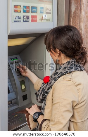 ZAGREB, CROATIA - JUNE 2, 2012: Unidentified girl withdrawing money from an ATM machine in city center. More than 4,000 ATM machines has been installed across Croatia since 1990.