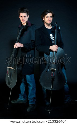 ZAGREB , CROATIA - March 23, 2011 : Croatian popular musician duo 2cellos with his instruments on black background  - stock photo