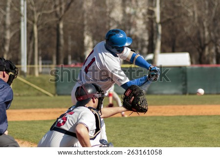 ZAGREB, CROATIA - MARCH 21, 2015: Match between Baseball Club Zagreb in blue jersey and Olimpija in gray jersey. Unidentified batter is about to hit the ball