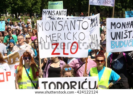 ZAGREB, CROATIA -MAY 21,2016:Protesters march with signs raised through Zagreb in a protest against US biotechnology group Monsanto and against TTIP agreement. A sign that says Monsanto American evil. - stock photo
