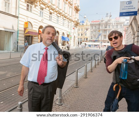 ZAGREB, CROATIA- MAY 23; Zagreb mayor, Milan Bandic on city street greeted by a local near the town square on May 23, 2011 in Zagreb, Croatia. - stock photo