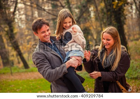 ZAGREB, CROATIA - 15 NOVEMBER 2015: Playfull family of three walk in a park on an autumn day. - stock photo