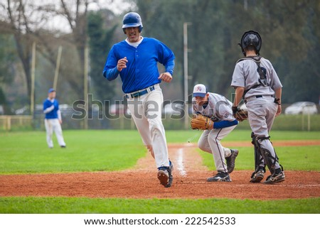 ZAGREB, CROATIA - OCTOBER 5, 2014: Croatian Cup Semifinal Tournament, match between Karlovac (grey jersey) and Sisak (blue jersey). Unidentified players runs to the base.