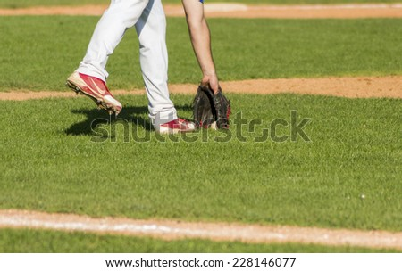 ZAGREB. CROATIA - OCTOBER 12, 2014: Match between Baseball Club Zagreb in blue jersey and Olimpija in dark blue jersey. Unidentified player pick up the ball