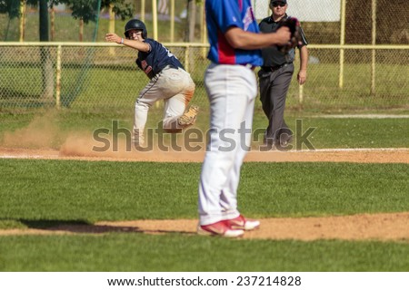 ZAGREB. CROATIA - OCTOBER 12, 2014: Match between Baseball Club Zagreb in blue jersey and Olimpija in dark blue jersey. Unidentified  runner on field