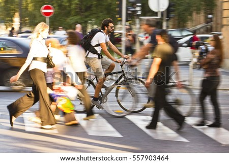 Zagreb, Croatia - September 4, 2011: Man riding a bicycle fast across the intersection between pedestrians on the streets of dowtown Zagreb on September 4, 2011.